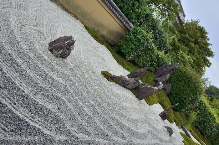 キリシタン大名である大友宗麟公が、1535(天文4)年に創建。 こちらの「独坐庭」は、荒波の中に佇む蓬莱山と島々を表現しています。波紋の躍動感から厳しい大自然を感じられるお庭です。 本堂裏にある「閑眠庭」は、7個の石を十字架の形に配置しています。