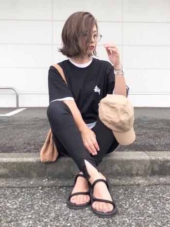 胸元にステューシーのロゴがワンポイントになった黒Tシャツの下に、ワンサイズ大きめの白Tシャツを重ね着しています。首元や袖口から覗かせるバランスが絶妙です。