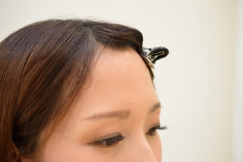 """前髪を真ん中分けにして、左右の髪をヘアクリップで留めます。分け目の中心が""""逆V字型""""になるように、コームの柄を使って左右少しずつ髪を引き出し毛束を取ります。"""