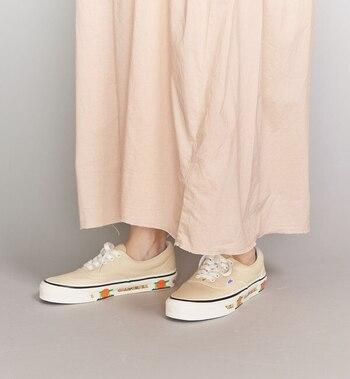 てろんとした生地が可愛いピンクベージュのスカートには、あえてカジュアルなアクセントが効いたスニーカーを合わせて。可愛すぎ防止にスニーカーはぴったりです◎