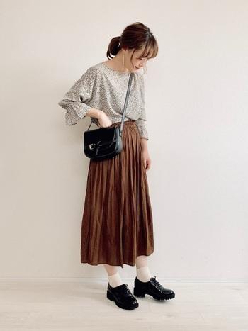小花プリントが可愛いボリュームスリーブブラウスに、ブラウンのスカートを合わせてシックな印象に。 黒小物で引き締めて、さらに大人感をアップさせるとおしゃれ。