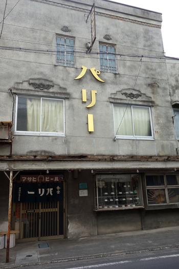 御花畑駅から徒歩約3分ほど、番場通りから1本入った路地にある「パリー食堂 」はレトロ感満載のお店。昭和2年に建てられた当時のままの姿で残っていて、国の登録有形文化財にも指定されています。