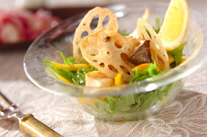 カットして混ぜ合わせた水菜と黄パプリカに、バターで炒めたエリンギと、揚げたレンコンをのせた見た目も華やかなサラダ。クシ切りのレモンを添えれば、見た目もよりさわやかになり、暑い日のごちそうサラダに最適かも。