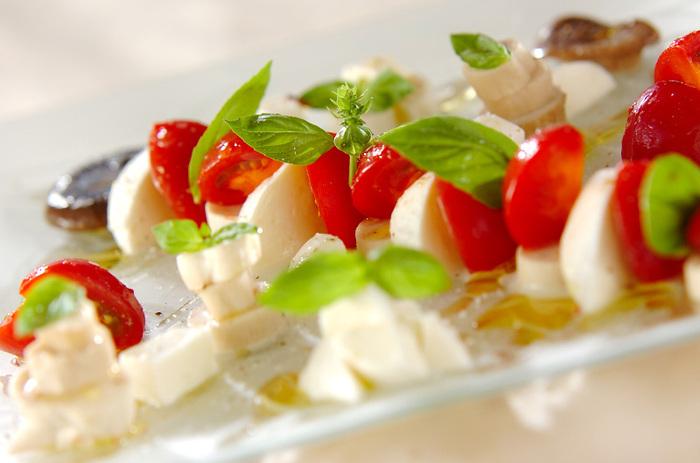 食卓が華やかになりそうなオシャレなサラダ。輪切りにしたエリンギとモッツァレラチーズの白、フルーツトマトの赤と、生バジルのグリーンの彩りも良く、簡単に作れるので、家飲みやランチ女子会メニューに覚えておくと◎。