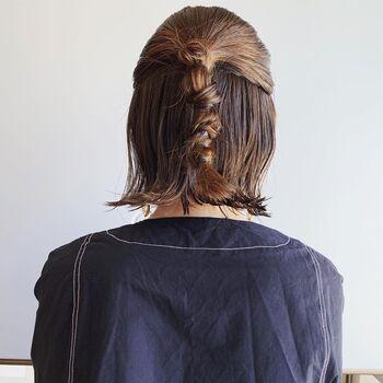 耳上の髪を後ろでひとつにまとめたら、二本に分けてねじってゴムで留め、さらにねじってゴムで留めを毛先まで繰り返します。あえてきっちりとまとめたハーフアップが、クールで大人っぽい雰囲気に。