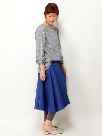 上品なグレンチェックのブラウスに、ブルーのスカートを組み合わせた爽やかなコーディネートです。リラックス感あふれる女性らしいシルエットが今年らしい印象。グレンチェックにカラーボトムスを合わせることで、いつもとは一味違うおしゃれな着こなしが楽しめますよ。