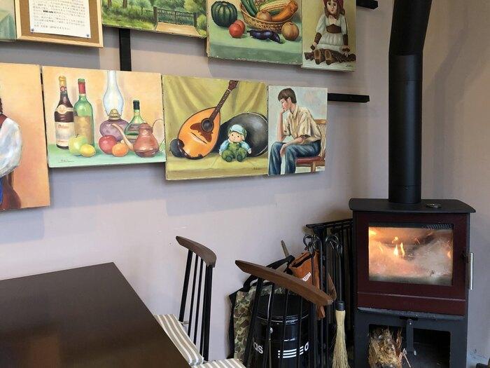 店内には月替わりで、軽井沢にゆかりのある作家さんの油絵や水彩画、写真、押し花など様々な作品が展示されています。趣のある薪ストーブもありますよ!