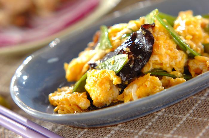 キクラゲの炒め物を作るときは、緑の野菜を入れると彩りがきれい。こちらは、たっぷりのごま油で作る絹サヤとキクラゲの卵炒め。酒と砂糖、醤油、オイスターに片栗粉を入れて、トロミを出して食材に味を絡めます。
