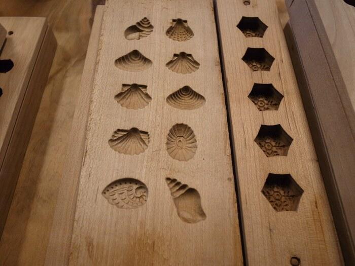"""干菓子に用いられる木型。  桜や樫(かし)等の堅い木に模様を彫り込むのは実に難しい作業です。京都市内には専門の職人はただ一人しかいないという話も耳にします。  """"打ちもの""""と呼ばれるのは、型に入れた菓子の生地を、まな板に""""打ち付けるように""""して取り出すことから。"""