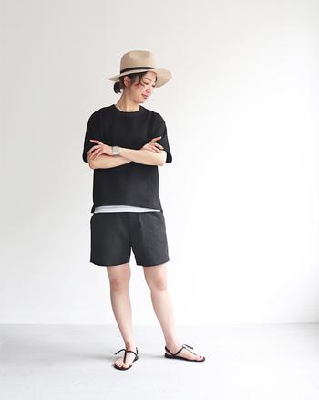黒のショートパンツに、黒のトップスを合わせたセットアップ風コーデです。インナーに合わせた白を裾から見せることで、ダークトーンに爽やかな差し色をプラスしたモノトーンコーデに。足元は黒のサンダルで、色味を合わせつつ軽やかにまとめています。