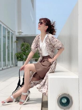 ブラウンのショート丈パンツに、花柄のワンピースを羽織りとしてプラス。インナーは白のVネックトップスで、涼しげ&トレンド感たっぷりなコーディネートです。
