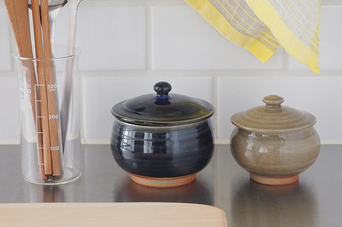 島根県江津市に窯を構える石州(せきしゅう)嶋田窯の「蓋つぼ」。キュッと丸みのあるデザインがかわいらしい「小」と、ぽってりとした下ぶくれの「大」。ついつい触れたくなるつまみがちょこんとのった蓋つき。