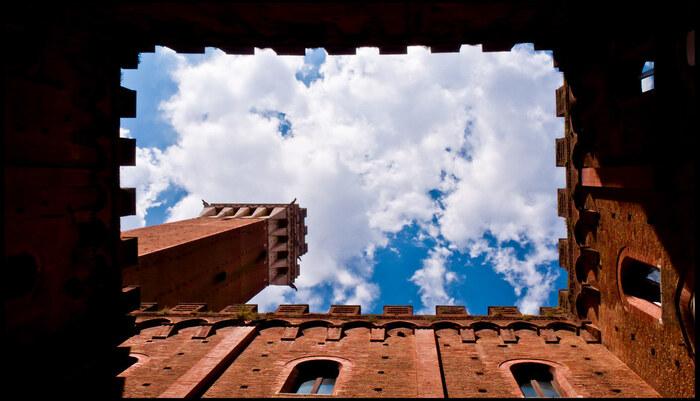 プッブリコ宮殿からマンジャの塔へ向かう途中にあるポデスタの中庭からマンジャの塔を見上げてみましょう。中庭を取り囲む飾り気の無い高い壁、長方形の枠から空とマンジャの塔が見えるだけの閉塞感は、厳しい思想が一般的であった中世特有の精神を静かに物語っています。