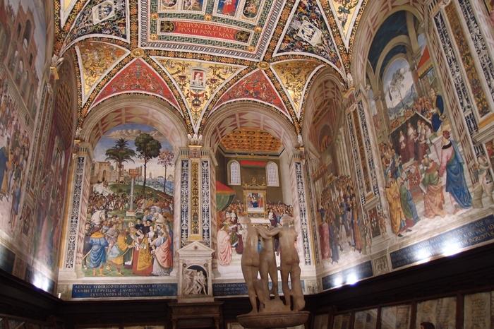シエナ大聖堂の内部には、床面のモザイク画をはじめ、天井、壁面など細部にまで緻密で豪華な装飾が施されています。その中でも、「ピッコローミニ家の図書館」と呼ばれる部屋は必見です。壁面を飾るフレスコ画の素晴らしさには、思わず息をすることさえ忘れてしまうほどです。