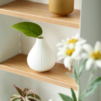 白地にストライプのような繊細なデザインと、丸みを帯びたシルエットが特徴的なフラワーベースです。ミニサイズなので一輪挿しにもぴったりで、グリーンやお花を上品に見せてくれます。