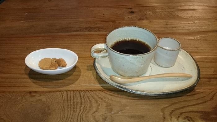 こちらが、店主さんが最もこだわりつくられている京都丹波産黒豆100%の「黒豆珈琲」。黒豆独特の優しく芳ばしい香りと、苦みと甘みが絶妙なまろやかな味わいが魅力です。  店主さん自ら黒豆珈琲の焙煎方法や挽き方を研究し、焼き加減を数段階に分けてプレンドするなど、試行錯誤の末に生まれたこだわりの逸品。ノンカフェインなので、時間やシーンを気にせず飲めるのも嬉しいですね。