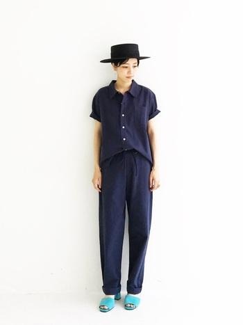 ブラックの麦わら帽子に、ネイビーのセットアップを合わせたコーデ。リラックス感の強い服なので、きちんと感のある帽子とサンダルでバランスを取ります。さらに足元にアクセントを加えても、コーデが華やかになりますね。
