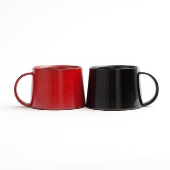 輪島塗で作られたマグカップは、朱と黒の二種類。緩やかに反った独特なシルエットや大きく作られた取っ手など、オリジナリティがあります。