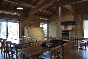 暖炉とアップライトピアノを備えたウッディな店内。すべてテーブルかカウンター席で、小上がりはありません。