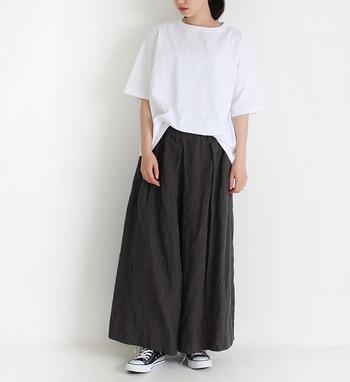 黒のワイドパンツに、ゆったりシルエットの白Tシャツをタックインしたモノトーンコーデ。足元は白と黒のスニーカーを合わせて、カジュアルな印象にまとめています。