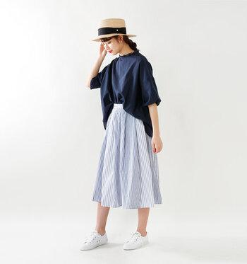 爽やかで涼しげなストライプスカートに、ネイビーのワイドシルエットトップスをフロントタックインした着こなしです。足元は白で爽やかにまとめて、ナチュラル素材のハットで季節を感じさせるコーディネートに♪