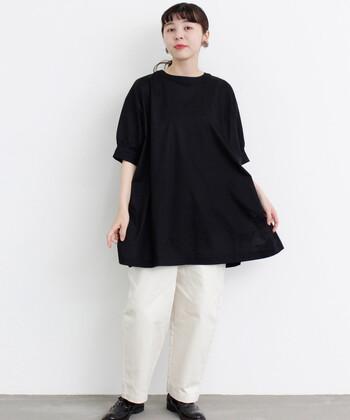 ちょっぴり長さのあるチュニック丈の黒トップスに、白のテーパードパンツを合わせたモノトーンコーデ。シューズも黒で合わせて、カジュアルとフェミニンの両立を叶えるベーシックな着こなしに仕上げています。