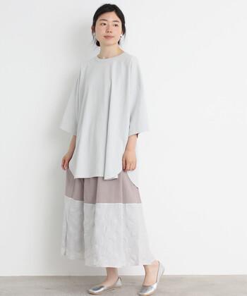 切り替えデザインが印象的なロングスカートに、ワイドシルエットの無地トップスを合わせた着こなし。あえてトップスをタックインしていないのが、今っぽコーデに仕上げるポイントです。