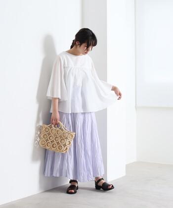 薄いパープルのロングスカートに、白のフレアブラウスを合わせたコーディネート。ナチュラル素材のバッグが、いいアクセントになっていますね。柔らかなカラーの組み合わせで、ふわっと風を感じさせる夏らしい着こなしに仕上がっています。