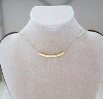 マットなゴールドパイプのネックレス。留め具がスライド式になっているので、服に合わせて長さを自由に変えられ、チョーカー風に付けることもできます。