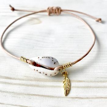 貝殻がワンポイントになった本革のブレスレットは、カジュアルなコーデにぴったり。ゴールドのフェザーが手の動きに合わせて揺れるのも魅力。