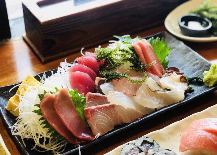 石垣島で海の幸を味わうなら、20年以上地元で愛され続けている「まぐろ専門居酒屋ひとし」がおすすめ。漁師から近海で採れたまぐろを直接仕入れているので、新鮮でリーズナブルな刺身や寿司がいただけます。かなり人気の高いお店なので、旅行に行く前から事前予約しておくと安心です。  画像は人気メニューの<刺身の盛り合わせ>。鮮度の高いお刺身を少しずつあれこれ食べられるのが嬉しいですね。沖縄ならではの海ぶどうも入っています。
