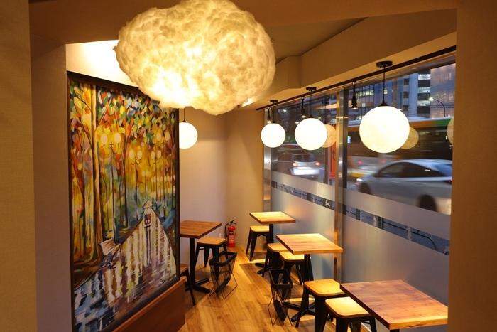 お店の中は、ダークな木と白い壁の落ち着いた雰囲気。暖色系のライトがあたたかい雰囲気を作り出します。イートインだけでなく、テイクアウトもOK。お持ち帰り用の袋もかわいいと人気です。