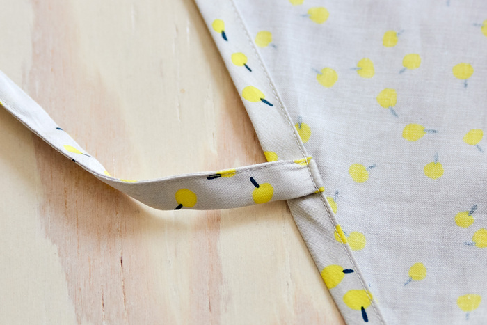 3.前身頃と同じように、後ろ中心側を三つ折りして縫う。このとき、後ろ紐付け位置(A・B)に紐を挟みながら縫う。