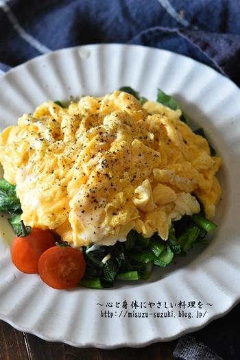5分で完成する小松菜と卵のサラダレシピ。  レンジで加熱した小松菜に、フライパンで火を通した卵をのせるだけでOK!卵にとろけるチーズを加えることで、まろやかで優しい味わいに。プチトマトを添えれば、さらに彩りが豊かになります。