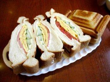 数あるメニューの中で1番人気は「ミックス・グリル・サンドウィッチ」です。運ばれてきて驚くのは、そのボリューム。パンは、ほぼ1斤分で分厚くカットされていて、中にはハムと卵、キュウリやトマトがたっぷりサンドされています。男性でも食べ切れないほどのボリュームなので、数人でシェアするのがおすすめ。