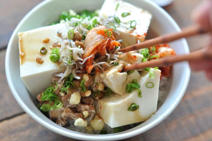 こちらも火を使わない、豆腐の丼レシピ。納豆やキムチ、薬味ねぎや揚げ玉などを、ごはんの上に用意したそれぞれの具材を盛り付け、しょうゆをかけて混ぜていただきます。お好みの具材で作れて、その組み合わせを考えるのも楽しい♪栄養もあり簡単なので、ランチや帰宅が遅いときの夜ご飯などにもおすすめです。