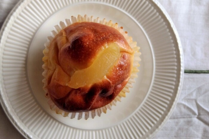 """薄くパンの皮に、りんごのコンポートが丸ごとくるまれて、ずっしり重たい♪""""芯""""の部分には優しい甘さのカスタードが詰まっています。(筆者撮影)"""