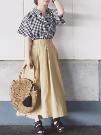 ギンガムチェックのブラウスに、ベージュのフレアスカート合わせたコーデ。 ウエストラインがしっかりとデザインされたスカートは、きちんと感があり、上品な雰囲気に。  大きめのラウンド型かごバッグが目を引くアクセントになっています。