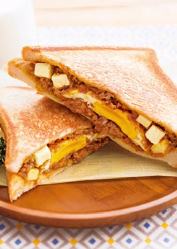 ひき肉や野菜を炒めて、カレールウなどで味つけしてキーマカレーに。チーズもプラスしておきます。それを目玉焼きとともに食パン2枚ではさみ、フライパンで両面こんがりと焼けばできあがり。