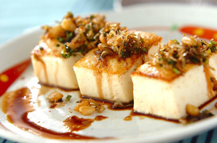シンプルで風味豊かなカリカリ豆腐ステーキ。炒めたちりめんじゃこや松の実をしょうゆやネギで炒め合わせ、焼いた豆腐の上にかけるだけ。お酒ともよく合います♬
