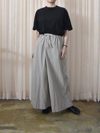 黒Tシャツをグレーのワイドパンツにタックインした、シックなフェミニンスタイル。足元も黒でまとめて、着ぶくれしがちなワイドシルエットのパンツをスッキリと着こなしています。