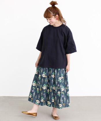黒のオーバーサイズTシャツに、花柄のロングスカートを合わせたコーディネートです。ネイビー系の色味を抑えたスカートなので、大人っぽく着こなせます。ゴールドカラーのパンプスが、程よく映えるワンポイントに。