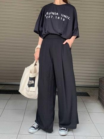 黒のロゴ入りTシャツに、ワイドパンツを合わせたワントーンコーデです。スニーカーも黒でまとめて、手に持った白系のトートバッグがナチュラル感をプラスする程よい差し色に♪