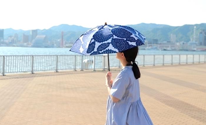 南国への旅で重宝するのは、晴雨兼用の日傘です。観光中の熱中症対策として強い日差しを避けたり、急な雨にも安心。折りたたみならば、使わないときも荷物にしまっておけます。  画像は、アザミの花のオリジナルプリントが美しい「breezy blue(ブリージーブルー)」の注染日傘です。注染には裏表が無いので、職人が一点一点手染めした柄を、日傘をさしながら楽しめます。