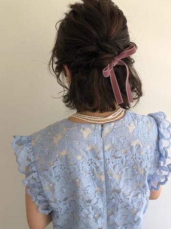 耳上の髪をねじりながら後ろでクロスさせて反対側の耳あたりでピンで固定させます。 ねじった毛束にリボンを通して結べば、一気に華やかパーティーアレンジに♪