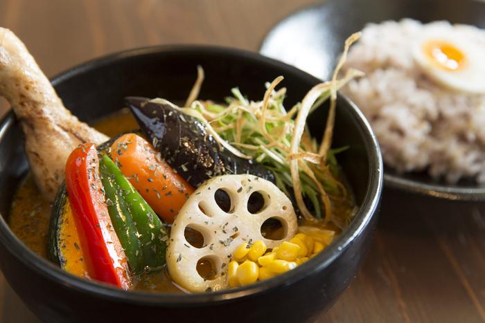 札幌発祥のスープカレー。ネパールやインド料理をベースに薬膳カレーとして作られたのが始まりだと言われています。スパイスの味や香りをストレートに感じられるサラサラしたスープと、ゴロゴロっと入った大きめの具材が特徴です。ご飯とスープは別に盛り付けて、ご飯をスープに浸して頂きます。