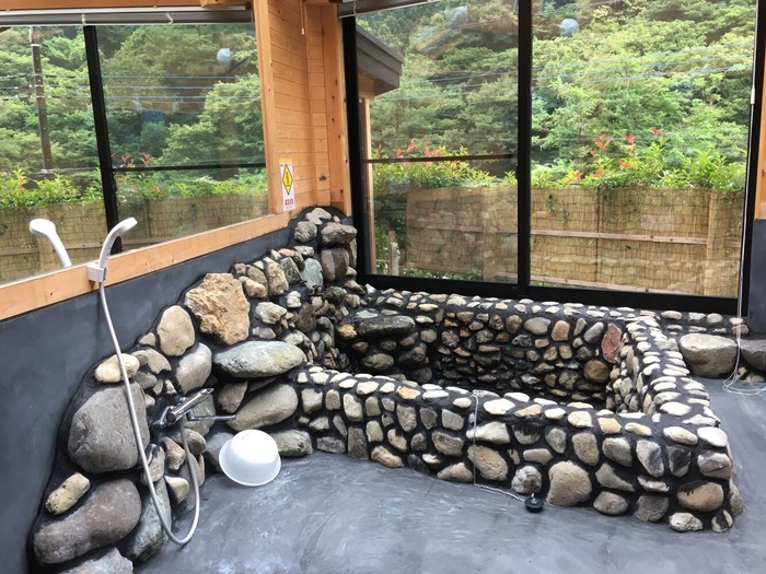 こちらは、宿の目玉でもある、大きな岩風呂。屋内ですが、ご覧の通り自然の景色を楽しめて、まるで旅館の露天風呂のよう*  ちなみに、3つ目のお風呂として、ユニットバスも完備。トイレは4か所(洋式)あり、プライバシーが確保されやすいのも、嬉しいポイント。お友達家族や三世代での旅行に、一押しです。