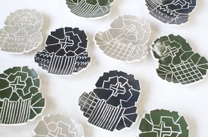 たんぽぽを幾何学模様風にアレンジしたプレートはあえて、色味をシックに。一見するとなんのかたちか分からないところがユニークですね。一枚だけ使うのはもちろん、色違いで何枚か、同じ食卓に並べてみるのも素敵です。