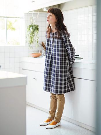 """秋ムードが高まるチェック柄は、スタンダードな配色が懐かしい雰囲気。綿のヘリンボーン生地にのせて、素朴な印象に仕上げています。 デザインは定番の""""割烹着ワンピ""""で、膝丈なのでボトムスを替えていろいろな着こなしが楽しめます。"""