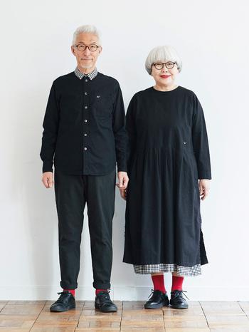 """夏に発売した「ponさんのギンガムワンピース」をベースに、首元を襟なしにアレンジしてすっきりと。スカート部分は2重にし、内側のギンガムチェックが裾とサイドスリットから覗き、レイヤード感が一枚で楽しめるようになっています。 トレードマークである""""めがね""""のワンポイント刺しゅうがさりげないアクセントに。 リンクコーデが楽しめるように、bonさんのシャツも襟だけギンガムチェックになっています。"""